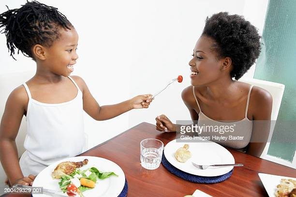 Girl (5-7) feeding mother tomato at dining table, smiling