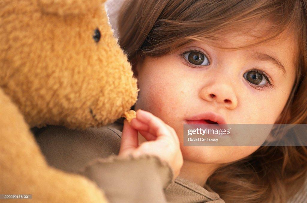 Girl (18-24 months) feeding stuffed toy, close-up