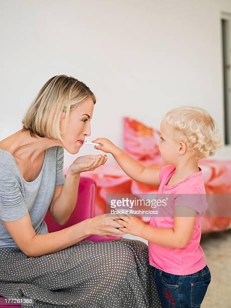 Girl feeding yogurt to her mother