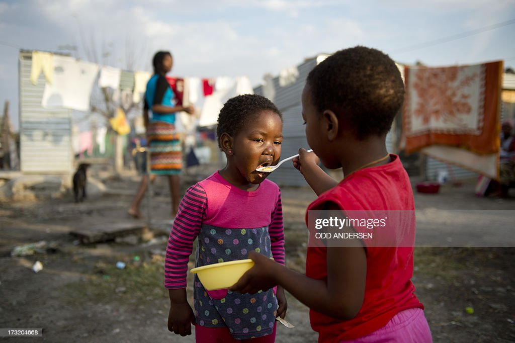 A girl feeds her sister on July 9, 2013 in the Nkaneng shantytown next to the platinum mine, run by British company Lonmin, in Marikana. On August 16, 2012, police at the Marikana mine open fire on striking workers, killing 34 and injuring 78, during a strike was for better wages and living conditions. Miners still live in dire conditions despite a small wage increase.