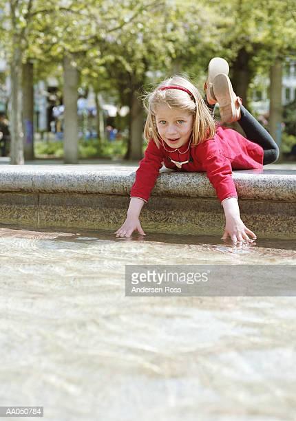 Girl (6-8) feeling water in wading pool, portrait