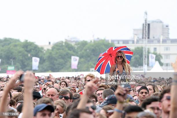 A girl festivalgoer is seen dancing with a union jack umbrella on someones shoulders at BT London Live celebration Concert at Hyde Park on August 12...