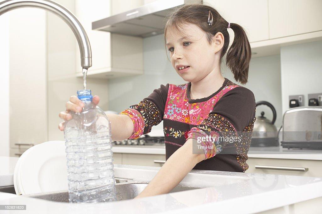 Girl filling up water bottle in kitchen