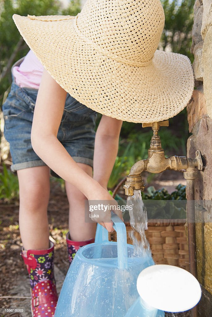 Girl filling up watering can at spout : Stock Photo