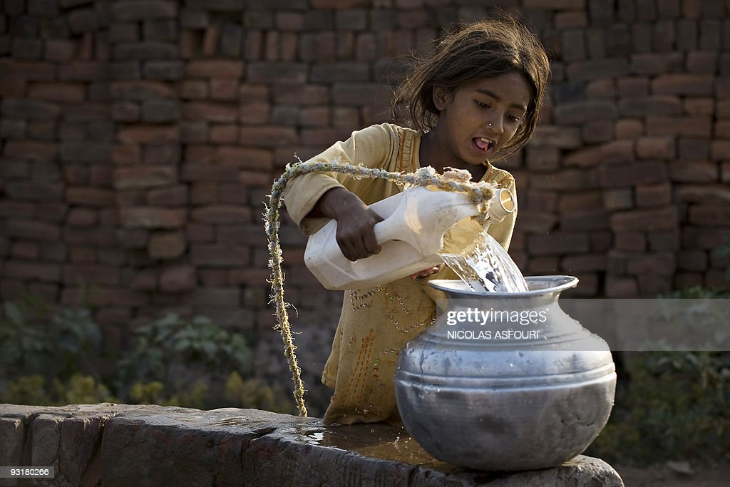 A girl fills up a jar from a well at the end of her work day at a brick factory in Rawalpindi on the outskirts of capital Islamabad on November 17...