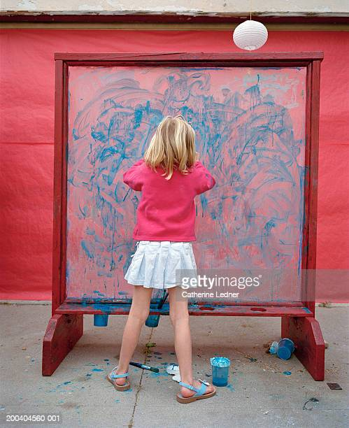 Girl (6-8) finger painting on easel, rear view