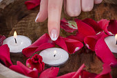 Woman finger with french nails polish style touch candle in bowl with water and red rose petals. Beauty and Manicure concept. Close up, selective focus