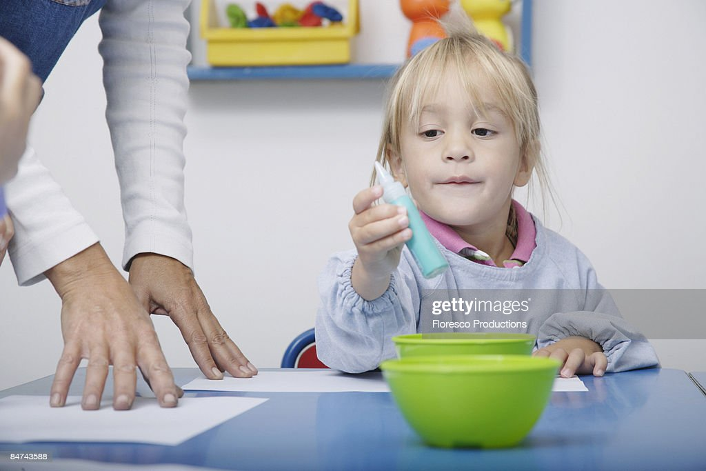 Girl finger-painting in classroom : Stock Photo