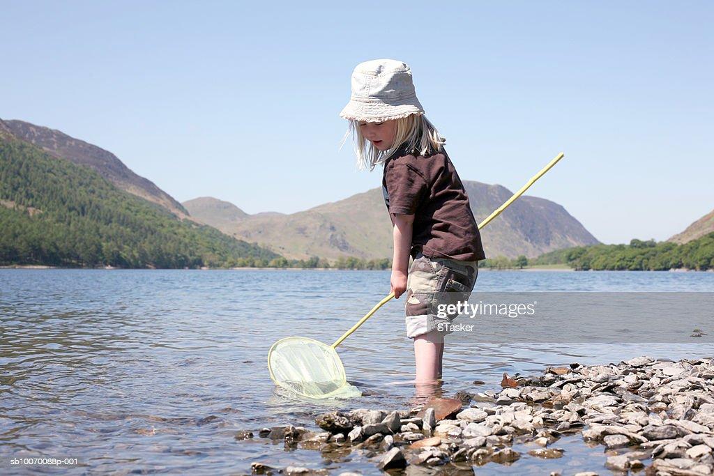 Girl (2-3) fishing in lake : Stock Photo
