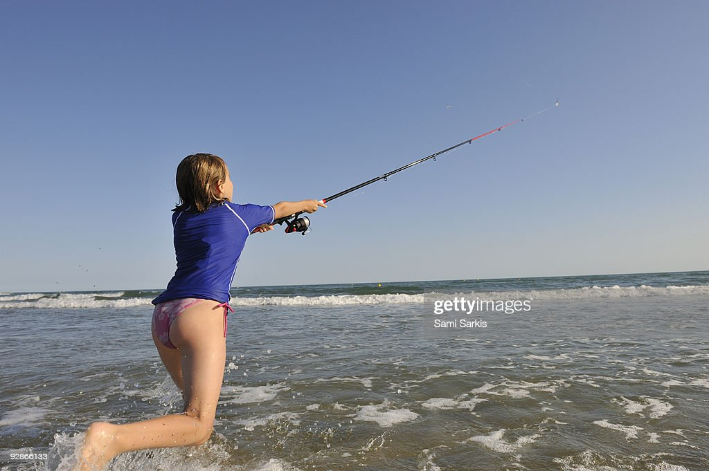 Girl fishing with reel rod from beach stock photo getty for Girl fishing pole
