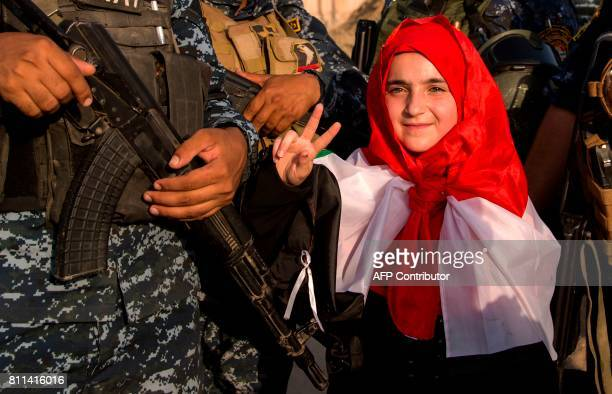 A girl flashes the victory sign as she stands by Iraq's federal police members celebrating in the Old City of Mosul on July 9 2017 after the...