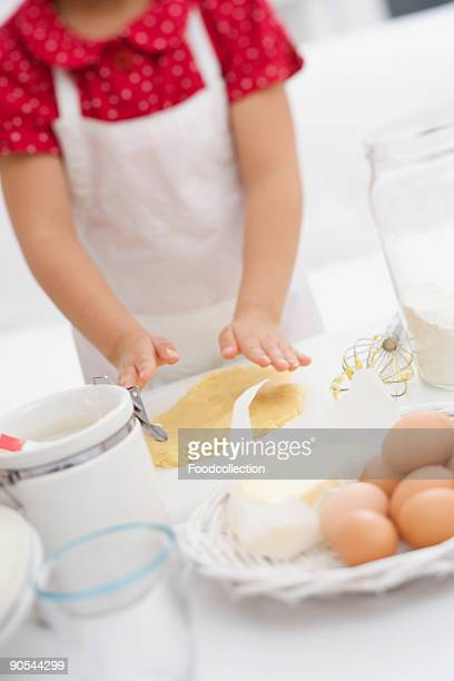 Girl (4-5) flattening dough with her hands, mid section