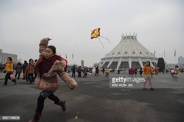 TOPSHOT A girl flies a kite as North Koreans come out to mark the start of 2017 on New Year's Day in Pyongyang on January 1 2017 / AFP / Kim WonJin