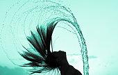 Silhouette of girl flipping her hair.