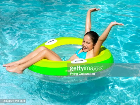Girl (8-10) floating in inflatable ring in swimming pool, smiling