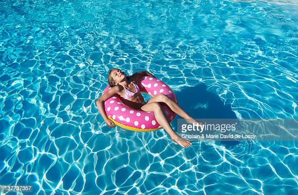 Fille à tube flottant dans la piscine