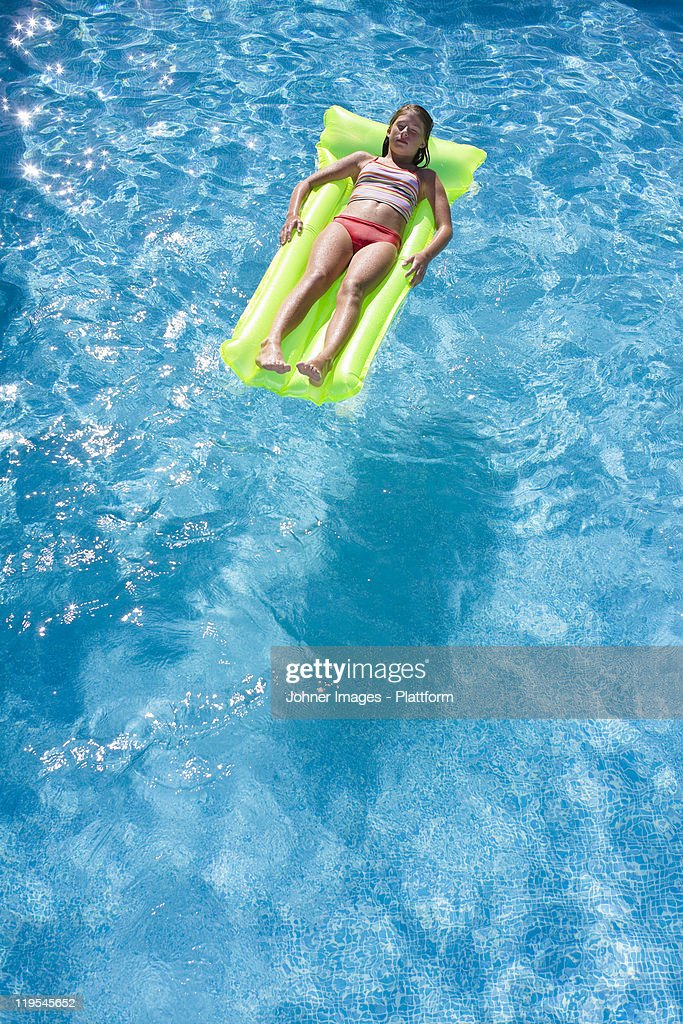 Swimming Pool Identification : Girl floating on inflatable raft in swimming pool stock