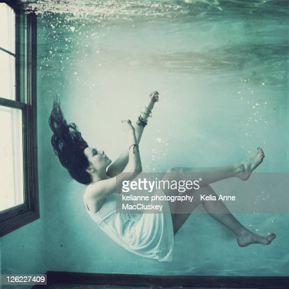 Girl floating underwater in house