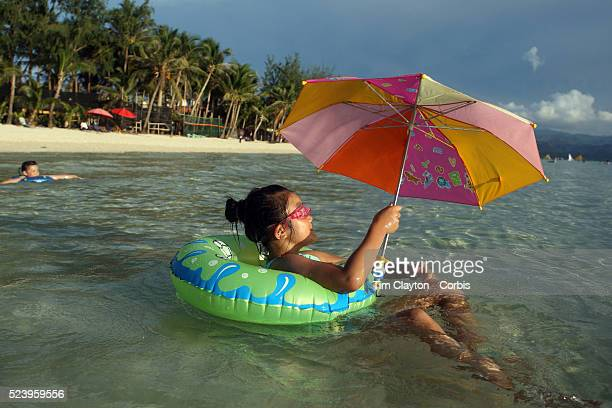 A girl floats with an inner tube in the pristine waters of White Beach with umbrella to protect her from the sun in Boracay Island the Philippines...