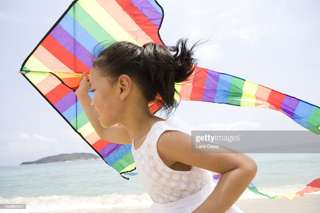 Girl flying a kite at the beach : Stock Photo