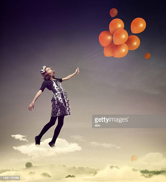 Girl flying in the air with balloons