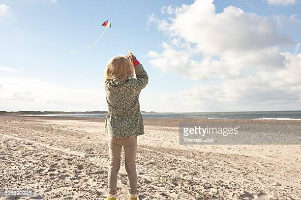 Girl flying kite on beach