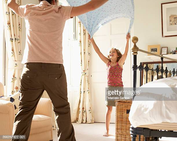 Girl (6-8) folding bedding with father, smiling