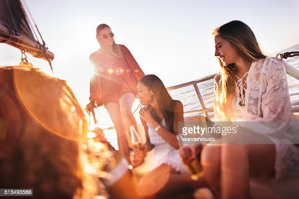 Girl friends drinking beer on sunset yacht cruise with sunflare
