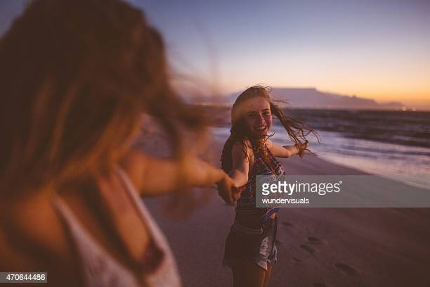 Girl friends having fun on the beach after sunset