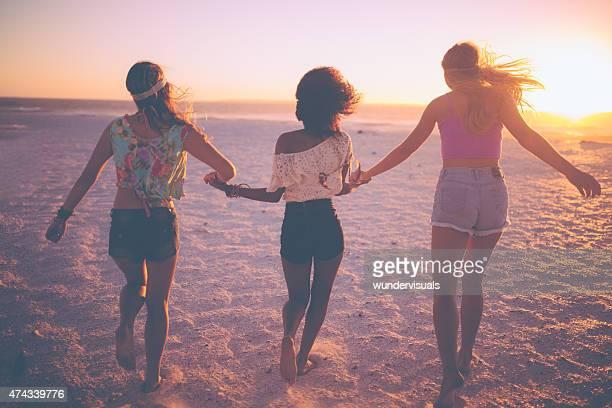 Fille amis courir en tenant les mains sur une plage au coucher du soleil