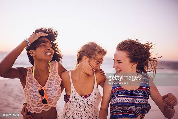 Girl friends walking together laughing on a windy beach