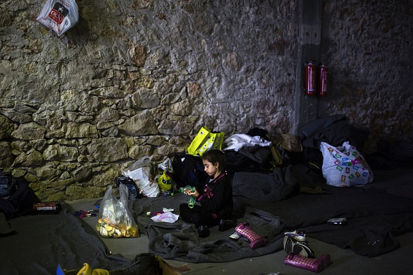 A girl from Afghanistan plays with a toy in a migrant and refugee makeshift camp inside a building at Piraeus harbour in Athens, on March 6, 2016. At least 25 migrants including children died on Ma...