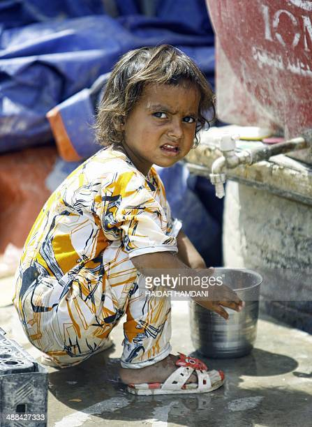 A girl from the Ghajar community squates near a stand pipe at their purposebuilt village close to Diwaniyah in southern Iraq on May 6 2014 The Ghajar...