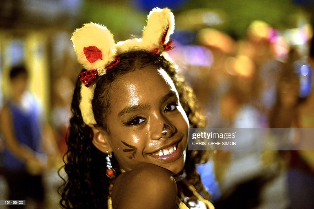 A girl from the local 'Indio' carnival group of the Guadalupe neighborhood in northern Rio de Janeiro, Brazil, takes part in their 'Bate Bola' traditional parade on February 10, 2013. AFP PHOTO/Christophe Simon