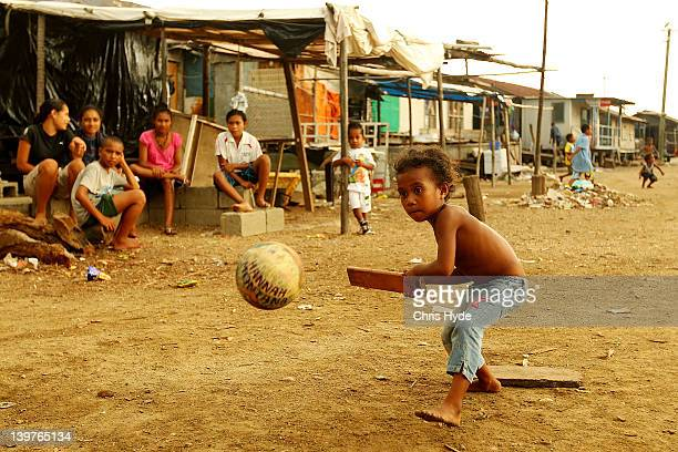 A girl from the village of Hanuabada bats during a game of cricket in the streets on February 24 2012 in Port Moresby Papua New Guinea