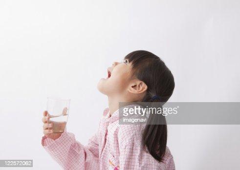 A girl gargleing her throat : Stock Photo