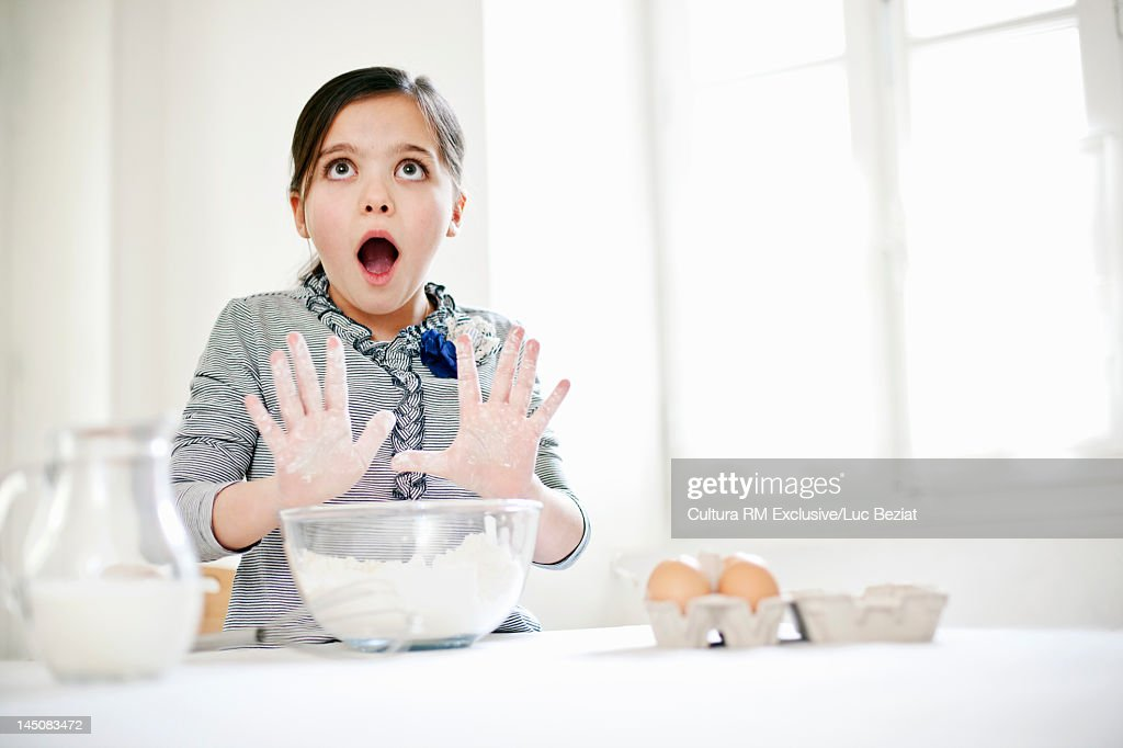 Girl gasping and baking in kitchen : Stock Photo