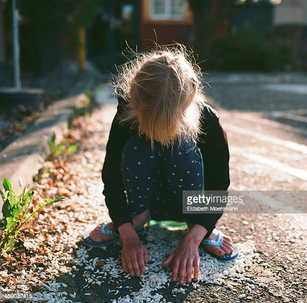 Girl gathering flower petals in hands