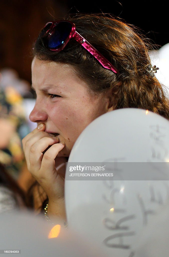 A girl gestures during a march along the Rio Branco avenue demanding justice and in homage to the victims of the Kiss nightclub fire, on January 28, 2013, in Santa Maria, southern Brazil, where a blaze on the eve killed more than 230 people. Brazilian police arrested four suspects --two of the Kiss club's owners, along with a pair of musicians who starred in the ill-fated pyrotechnic show, in the wake of the nightclub fire that forced sports officials to defend preparations for the World Cup and Olympics.