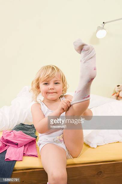 Girl getting dressed on bed, putting on socks