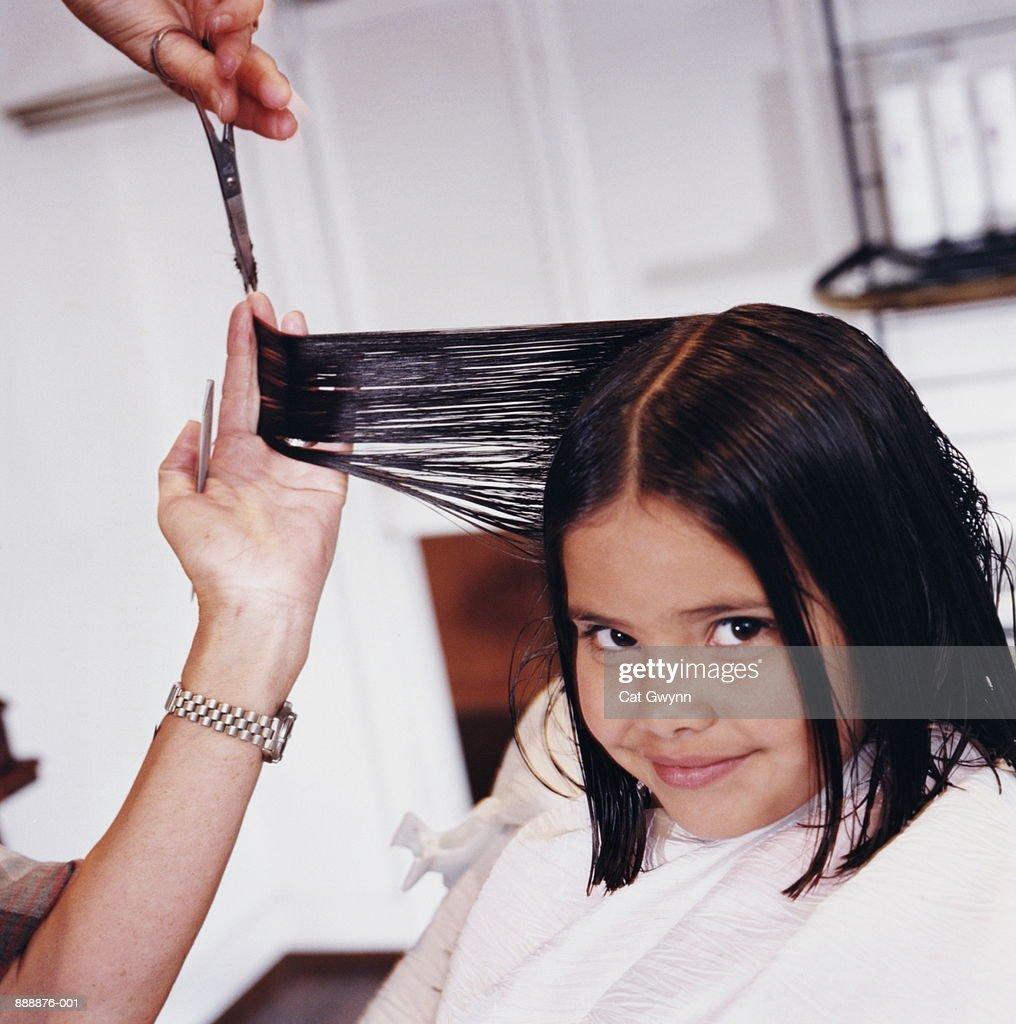 Girl (6-8) getting haircut : Stock Photo