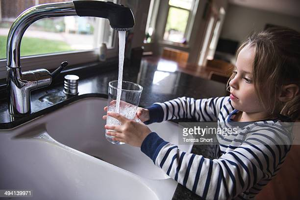 Girl getting water from kitchen sink