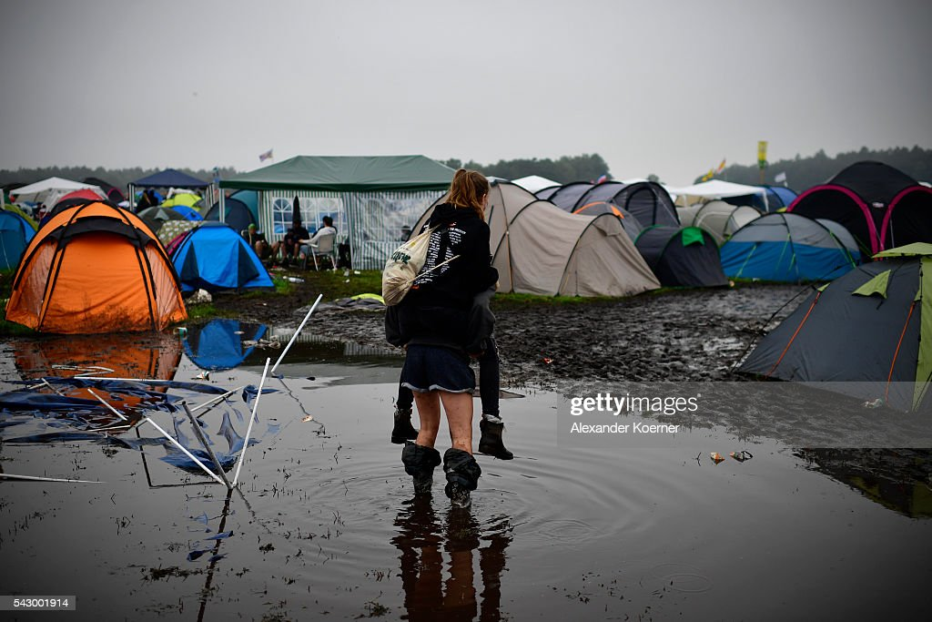 A girl gives another girl a piggyback ride through a puddle at the flooded camping compound at the Hurricane Festival compound on June 25, 2016 in Scheessel, Germany. The Hurricane Festival was evacuated yesterday and was delayed today for the late evening, following heavy rain and thunderstorm alerts. The rain and thunderstorm have hit the festival during the night and day, causing damage to tents and flooded the festival site, only 7 concerts can be played on two stages today. The Hurricane Festival celebrates this year its 25th anniversary. 75.000 music fans have visited the Festival, but some thousands have already left the compound due to the current situation.