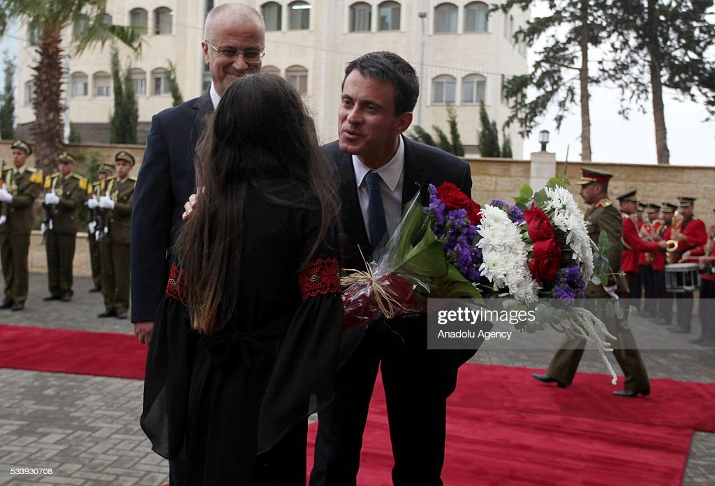 A girl gives flower to French Prime Minister Manuel Valls (R) as he is welcomed by Palestinian Prime Minister Rami Hamdallah (L) in an official welcoming ceremony at Prime Minister's Residence in Ramallah, West Bank on May 24, 2016.