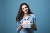 Cute girl giving a beautiful gift box with pink ribbon