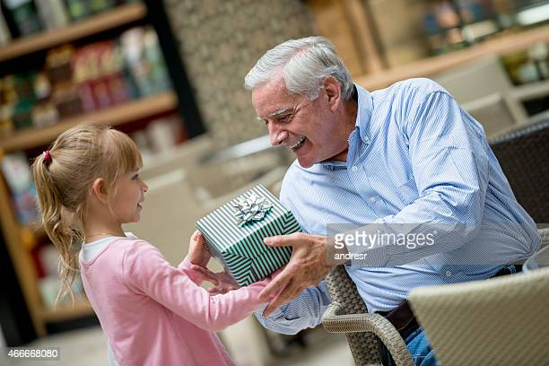 Girl giving a present to her grandfather