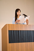 Girl giving a speech on stage, colored background