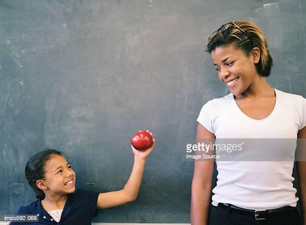 Girl giving an apple to teacher