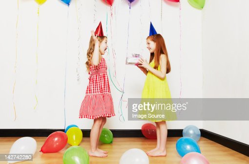 Girl giving birthday gift to friend : Stock Photo
