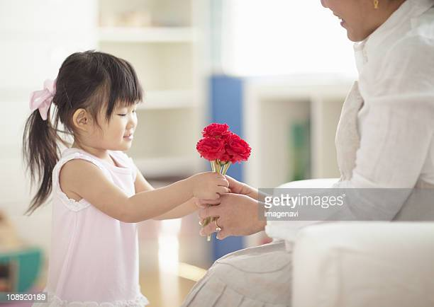 Girl giving carnation flowers to her mother